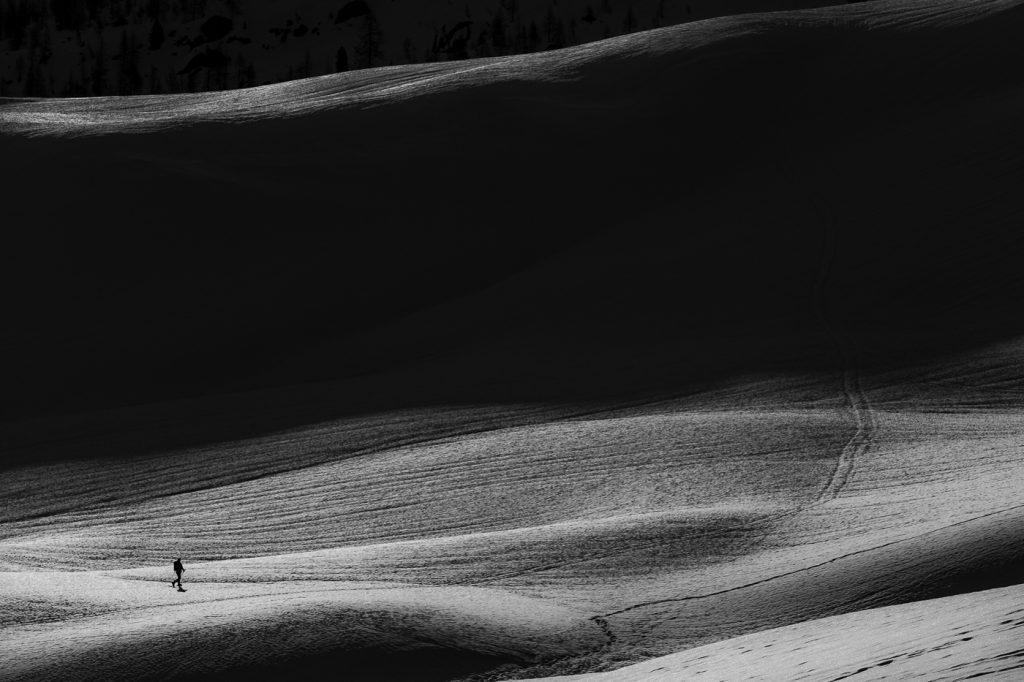 Mała sylwetka skiturowca wspinającego się na górę
