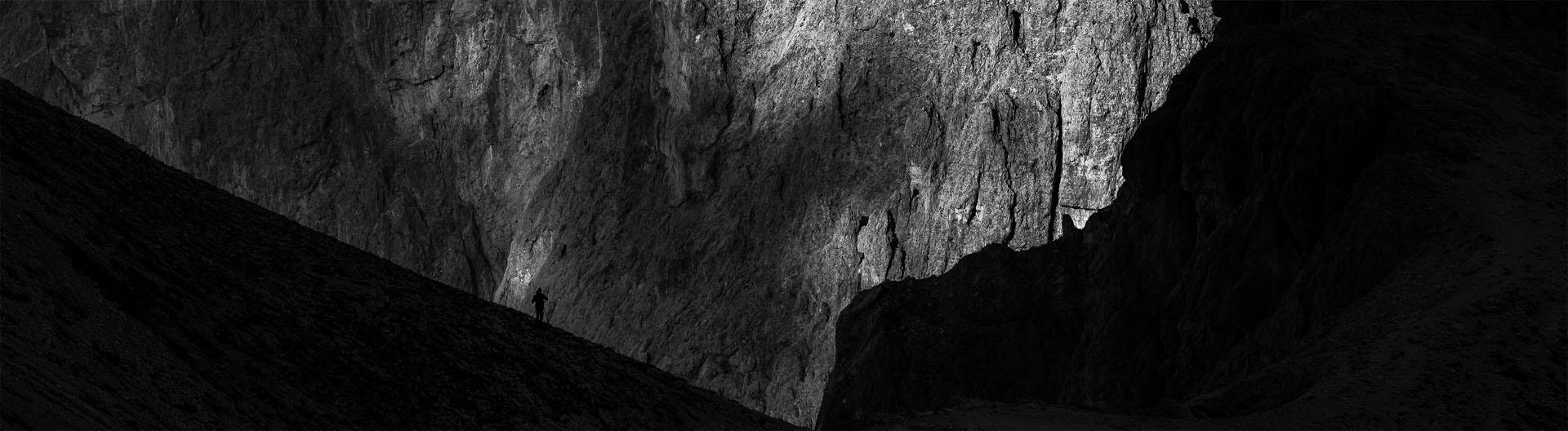 Czarno-białe zdjęcie sylwetki fotografa w Dolomitach na tle gór